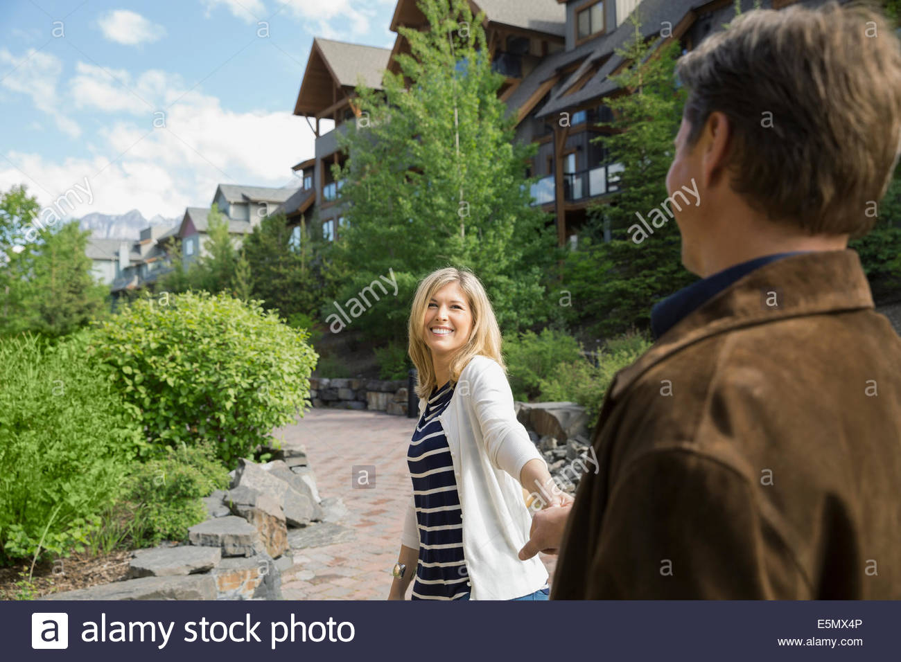 Couple holding hands outside hotel - Stock Image
