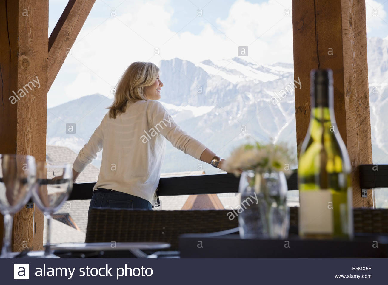 Woman on balcony looking at mountain view - Stock Image