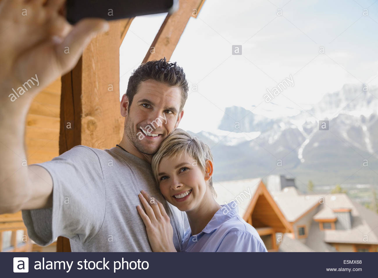 Couple taking selfie on balcony with mountain view Stock Photo