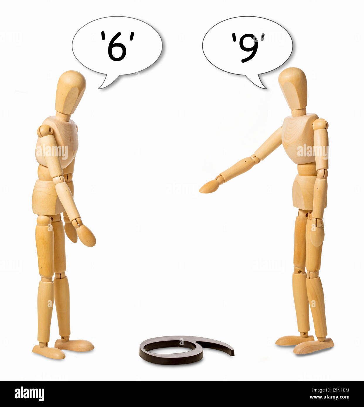 two mannikins arguing whether a number on the floor is a 6 or a 9 - Stock Image