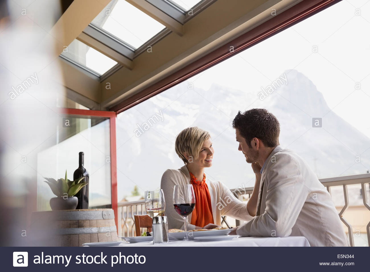 Romantic couple at restaurant table on balcony - Stock Image