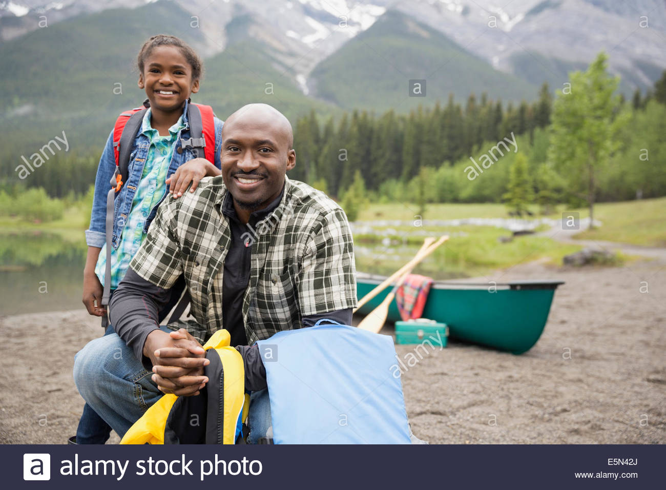 Portrait of father and daughter near canoe - Stock Image