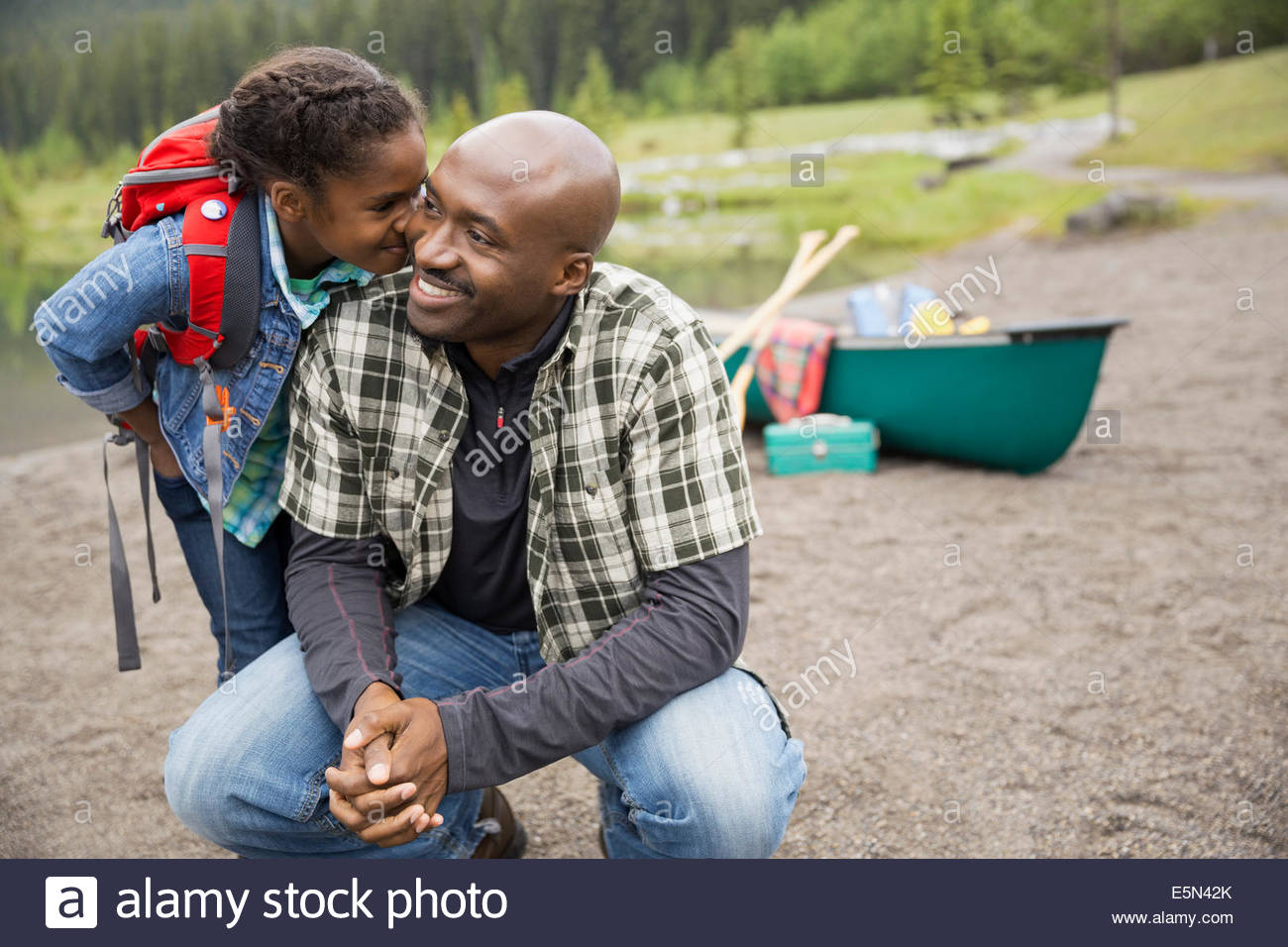 Daughter kissing father near canoe - Stock Image