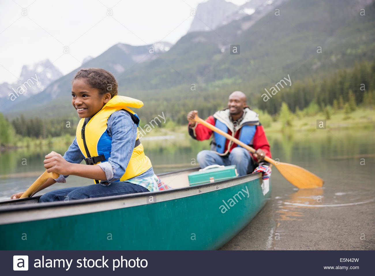 Father and daughter canoeing in lake Stock Photo