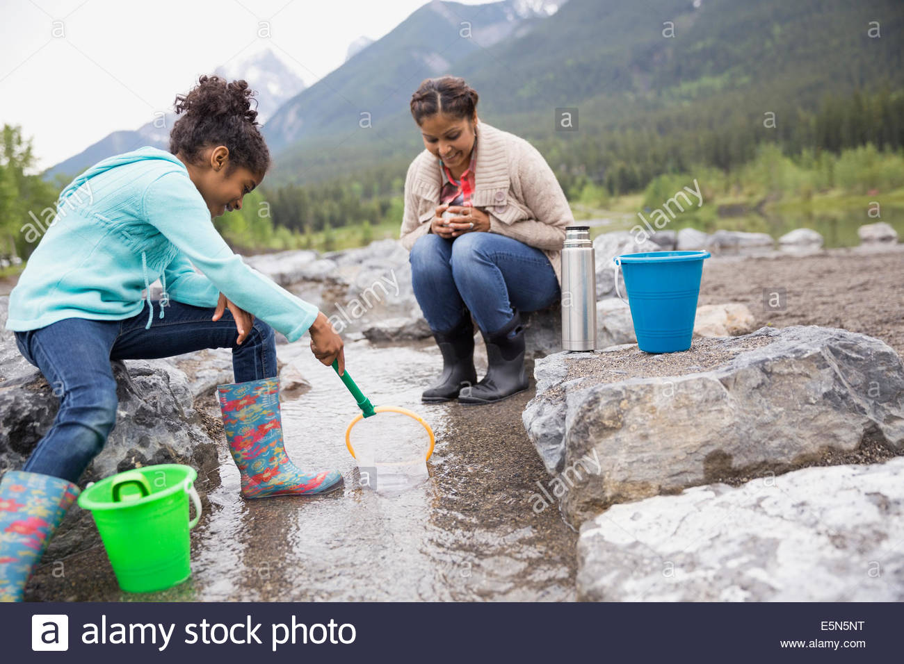 Mother and daughter fishing at stream - Stock Image