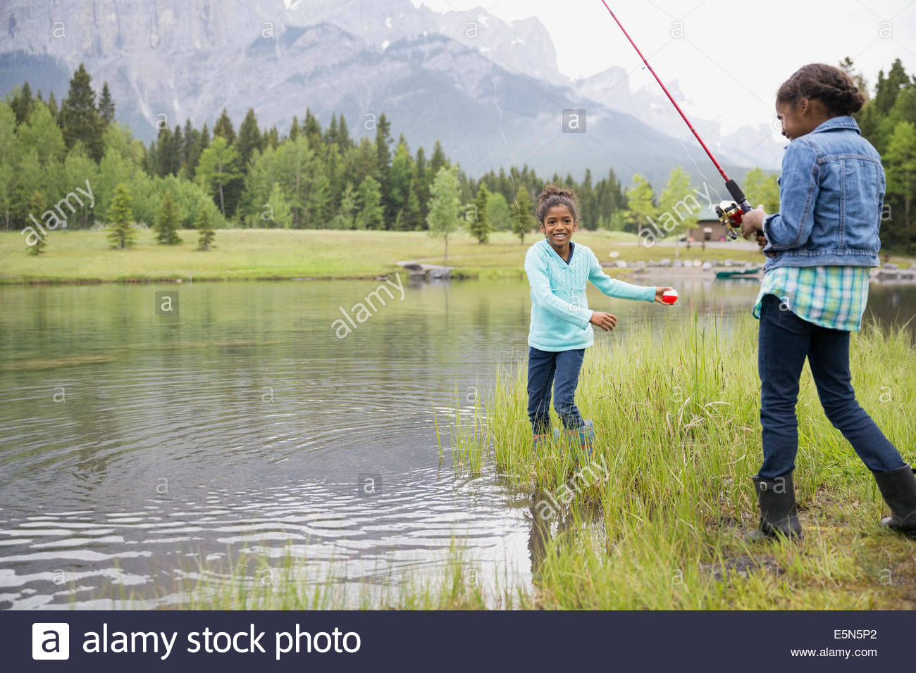 Sisters with fishing rods fishing at lakeside - Stock Image