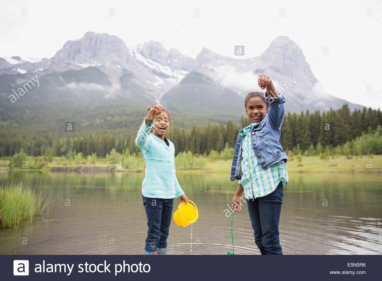 Portrait of sisters holding small fish in lake - Stock Image