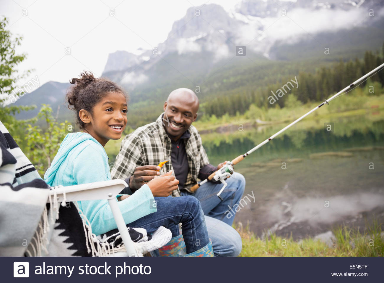 Father teaching daughter to fish at lakeside - Stock Image