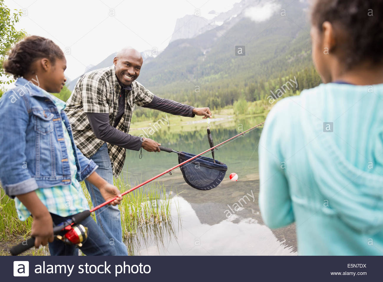 Father and daughters fishing at lakeside - Stock Image