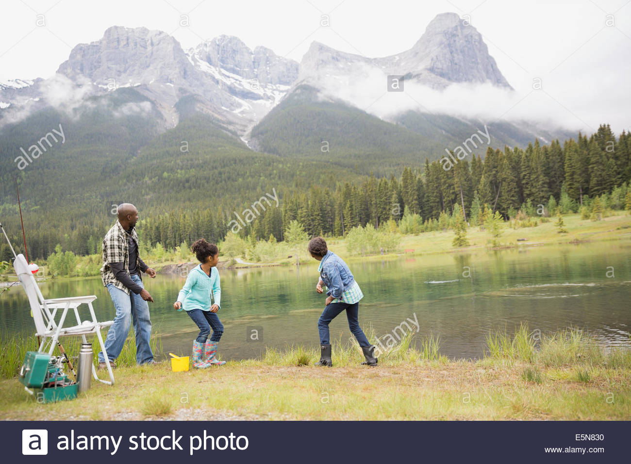 Father and daughters throwing stones in lake - Stock Image
