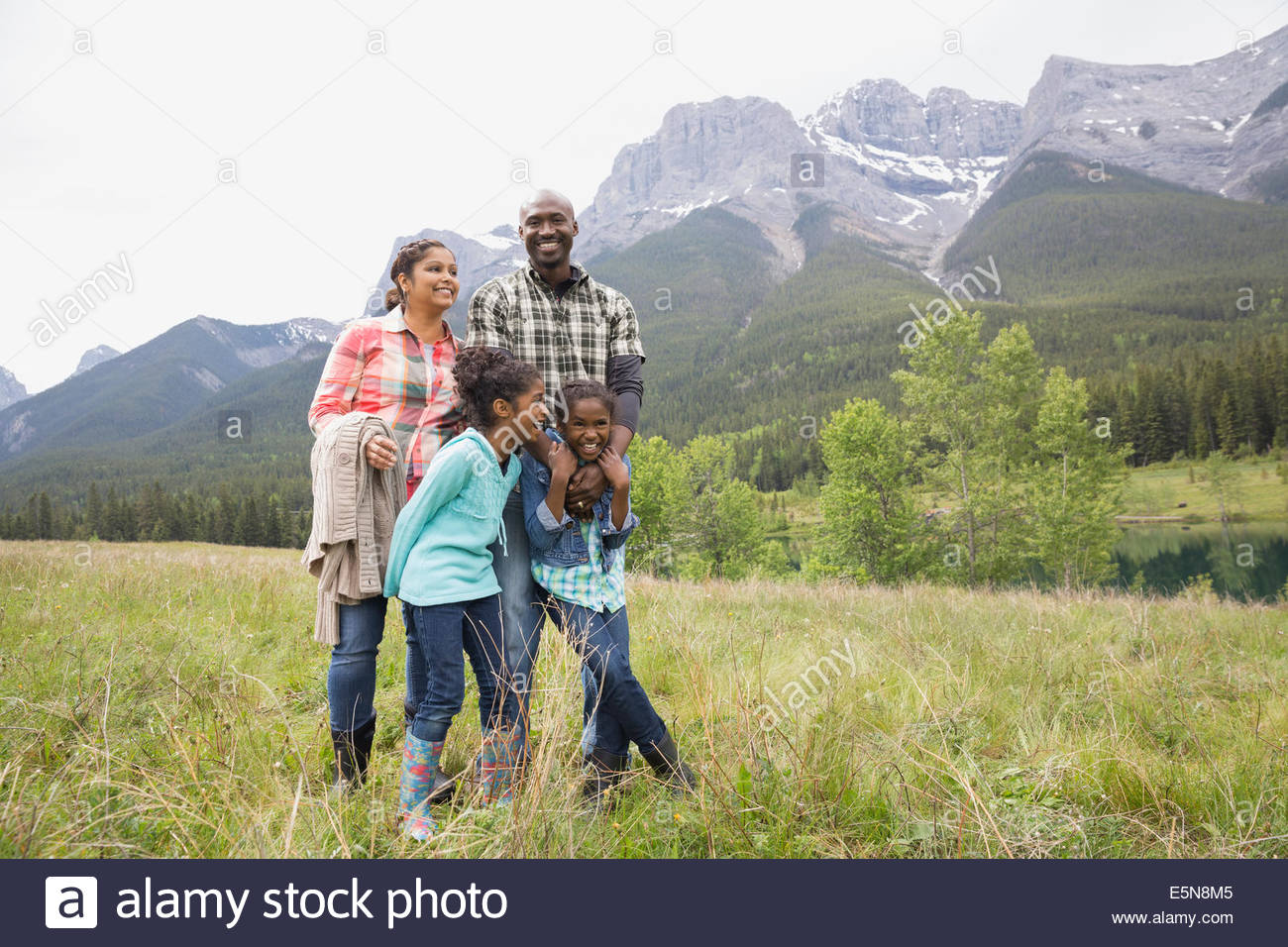 Family standing in grassy field - Stock Image
