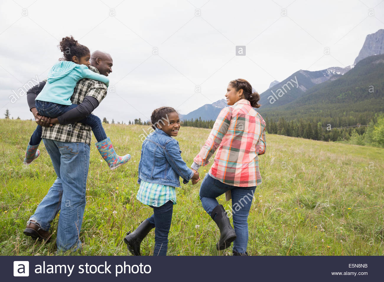 Family walking in grassy field - Stock Image