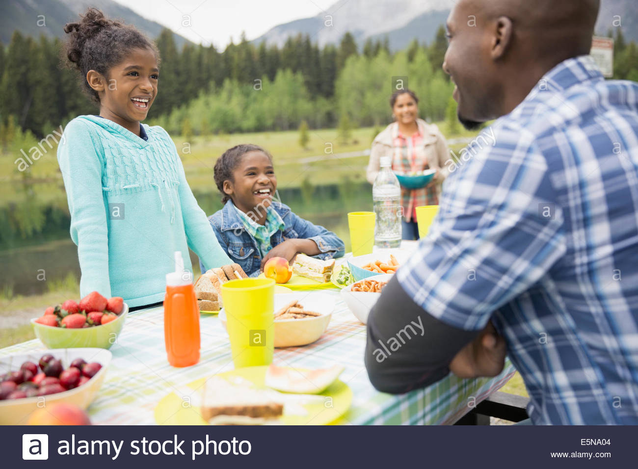 Family eating at picnic table - Stock Image