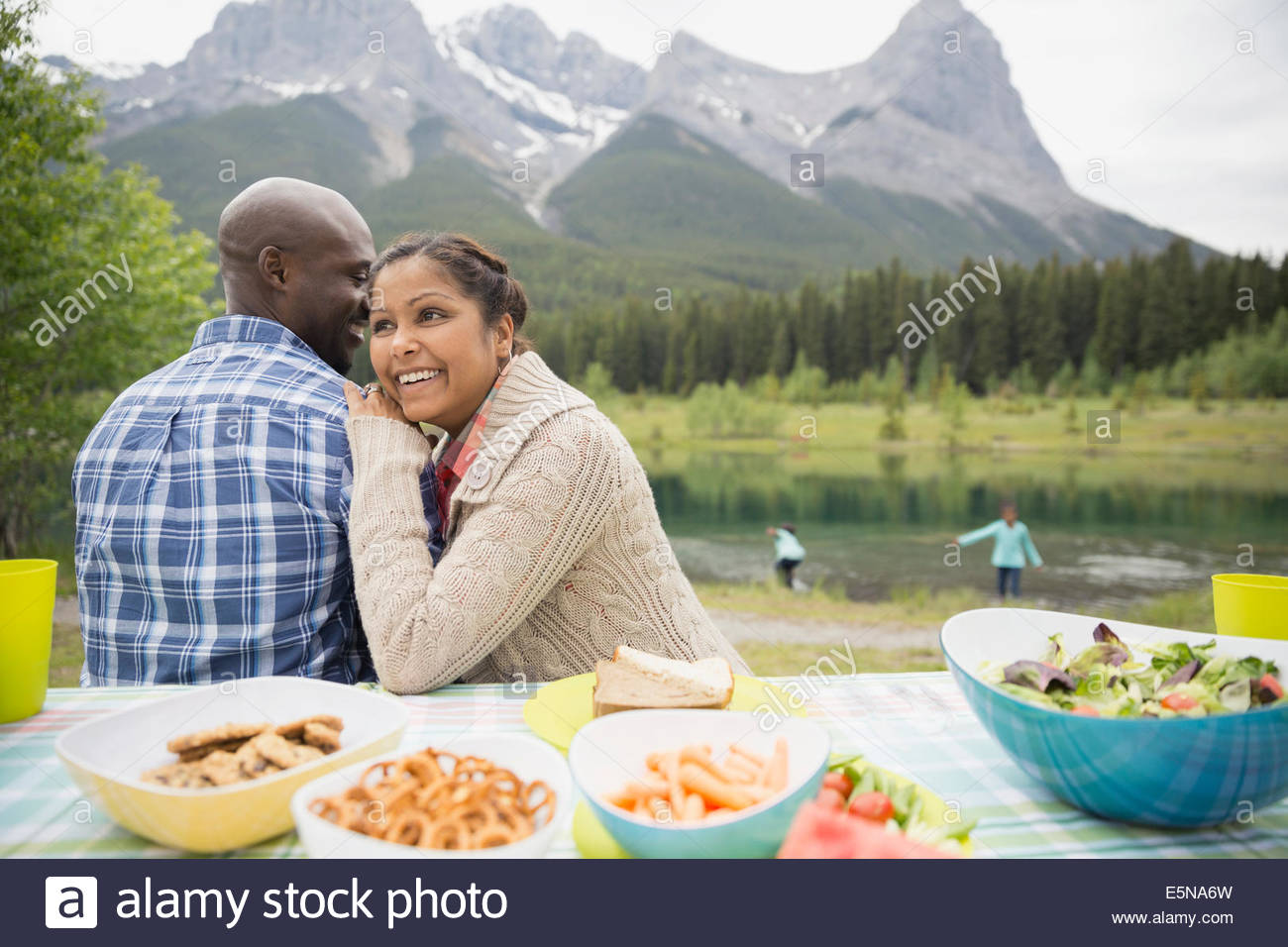 Couple sitting at picnic table near lake - Stock Image