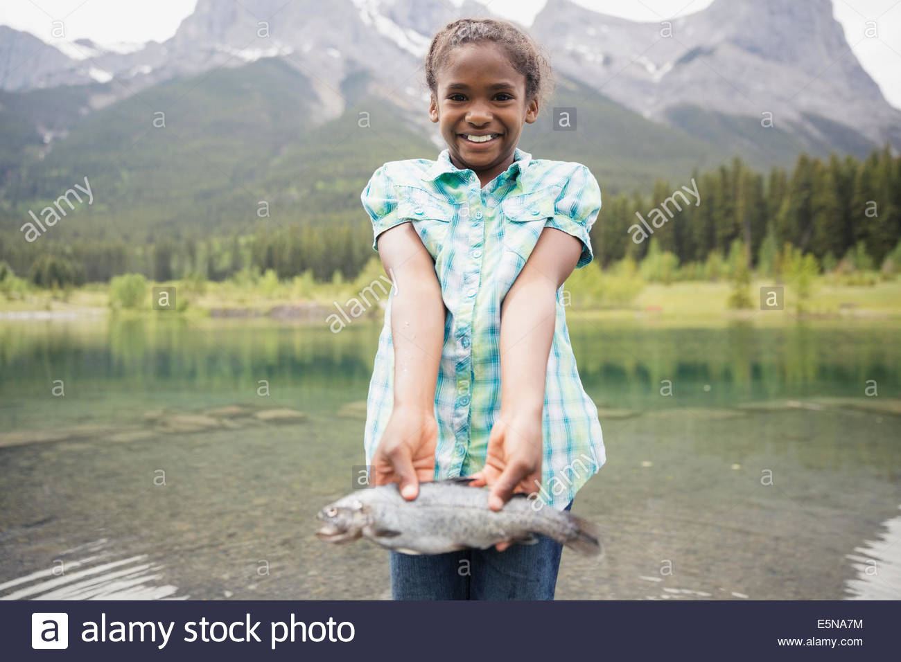Portrait of proud girl holding fish at lake - Stock Image