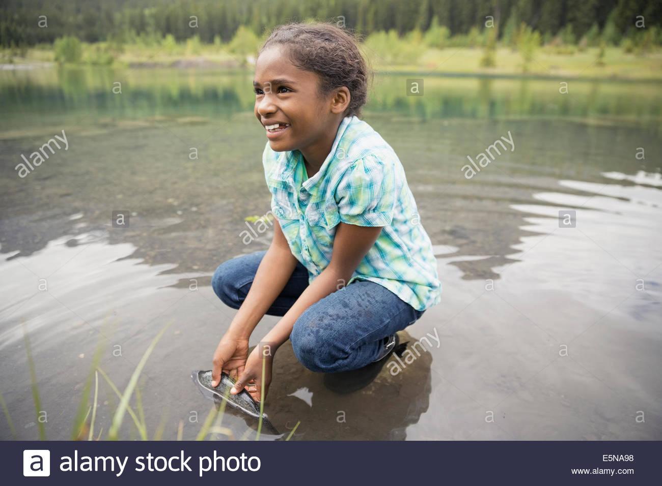 Smiling girl catching fish in lake - Stock Image