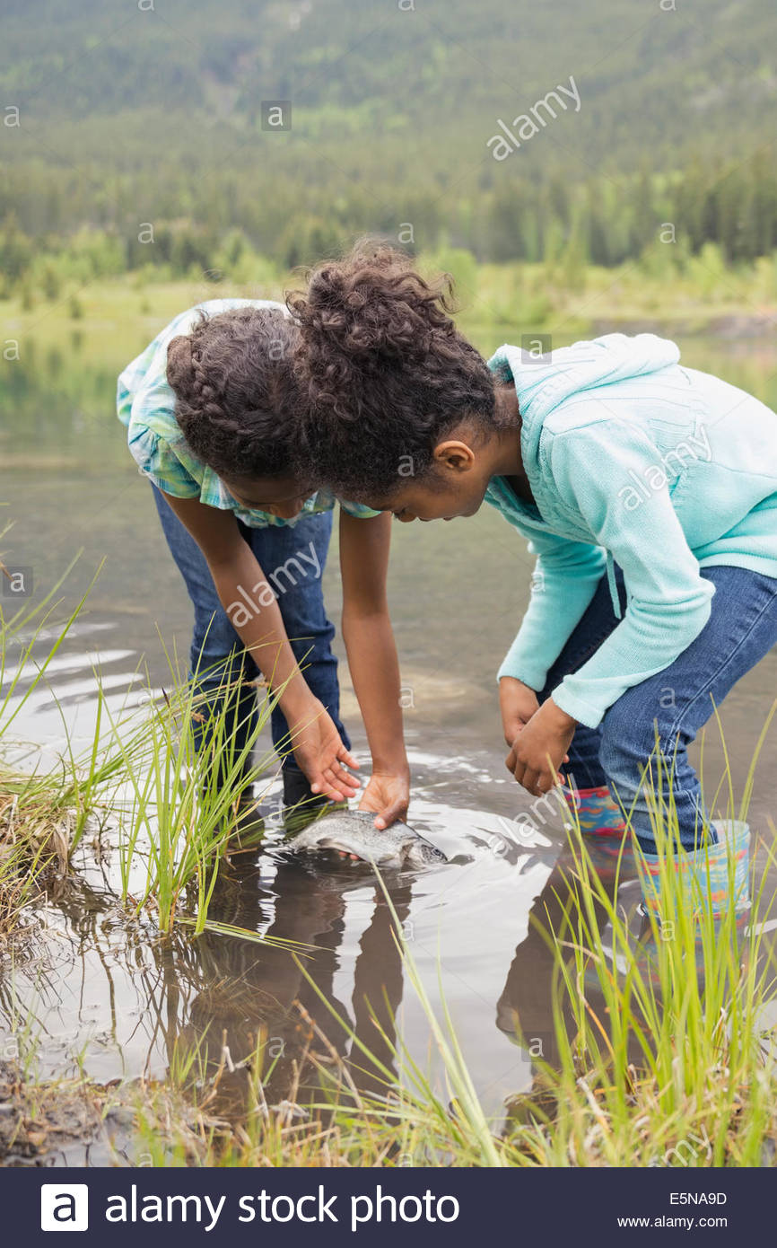 Girls catching fish in lake - Stock Image