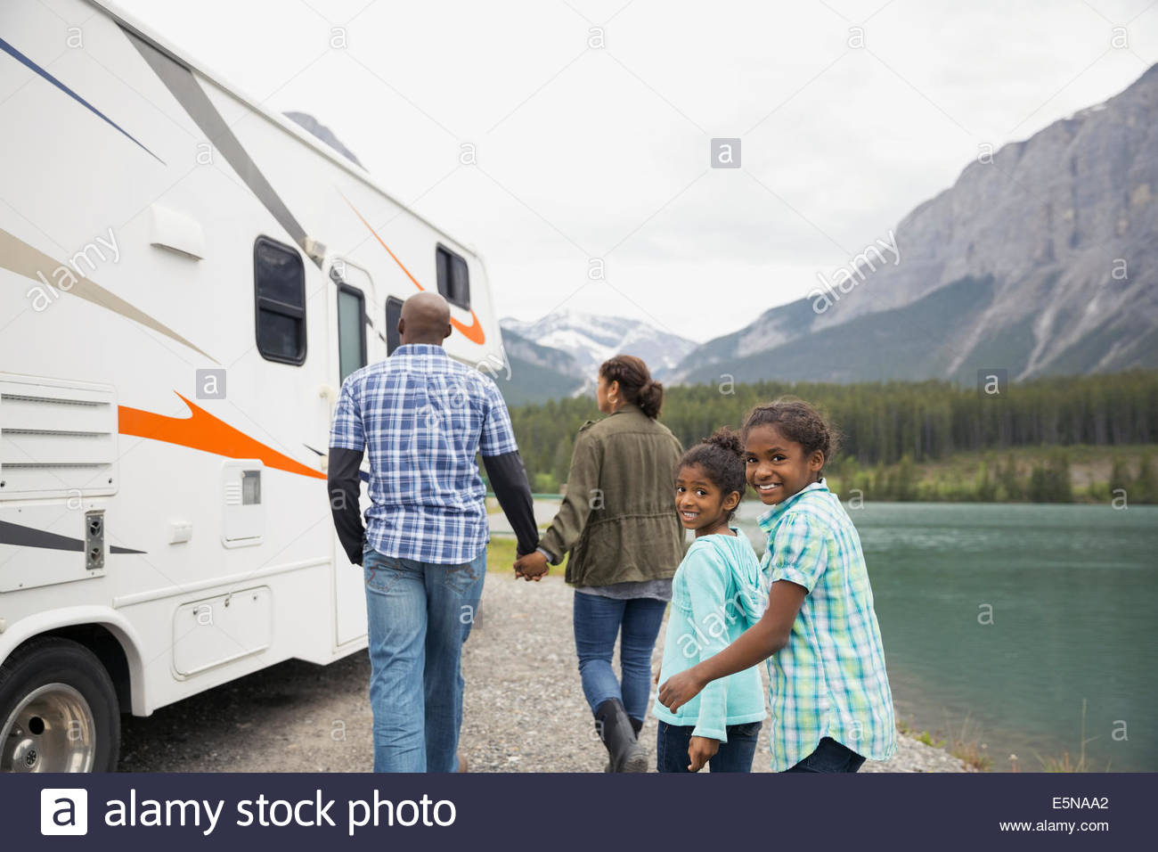 Family at lakeside walking toward RV - Stock Image