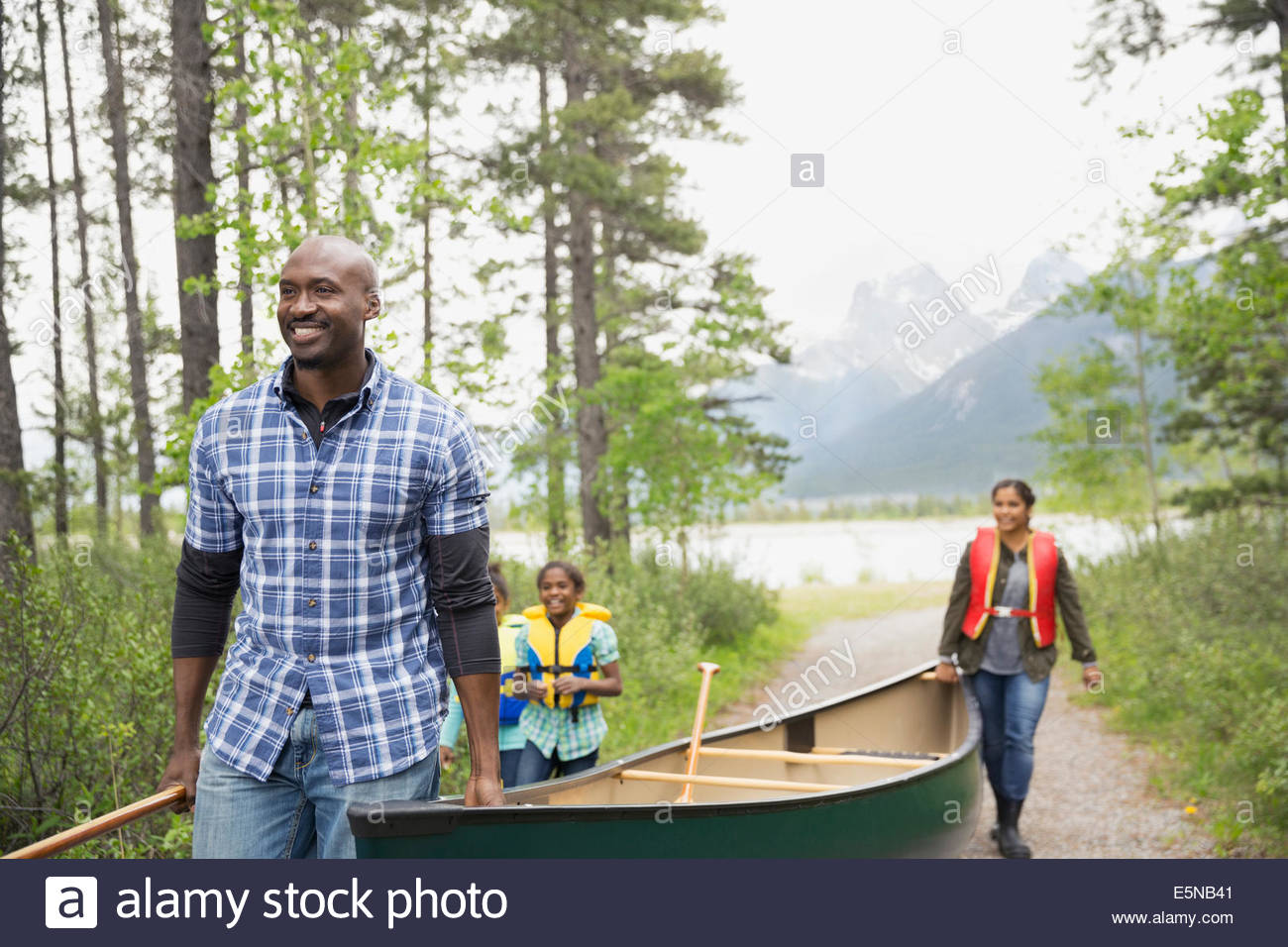 Family carrying canoe away from lake - Stock Image