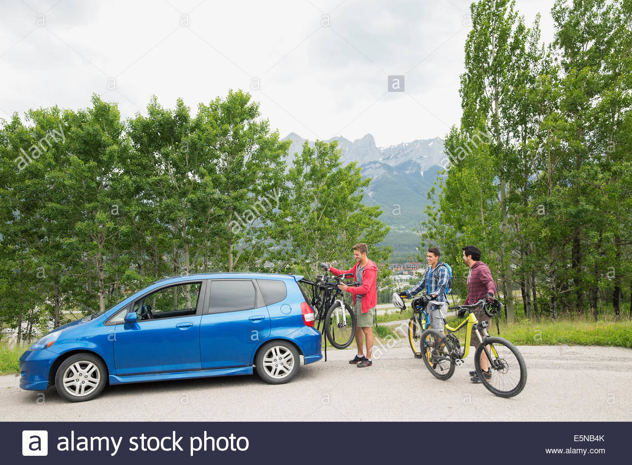 Men removing bicycles from bike rack on car - Stock Image