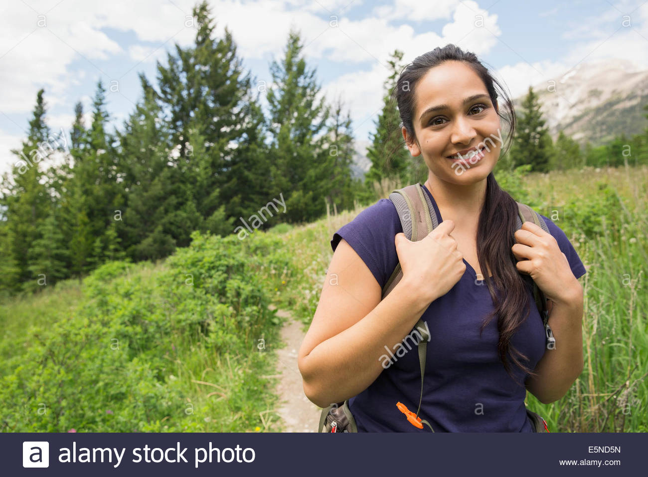 Portrait of smiling woman on hiking trail - Stock Image