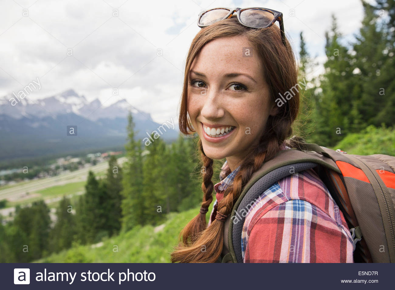 Portrait of smiling woman hiking near mountains - Stock Image