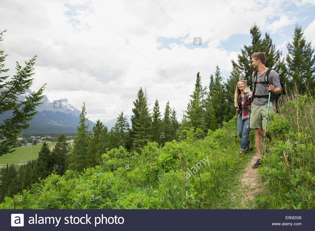 Couple hiking on trail near mountains - Stock Image