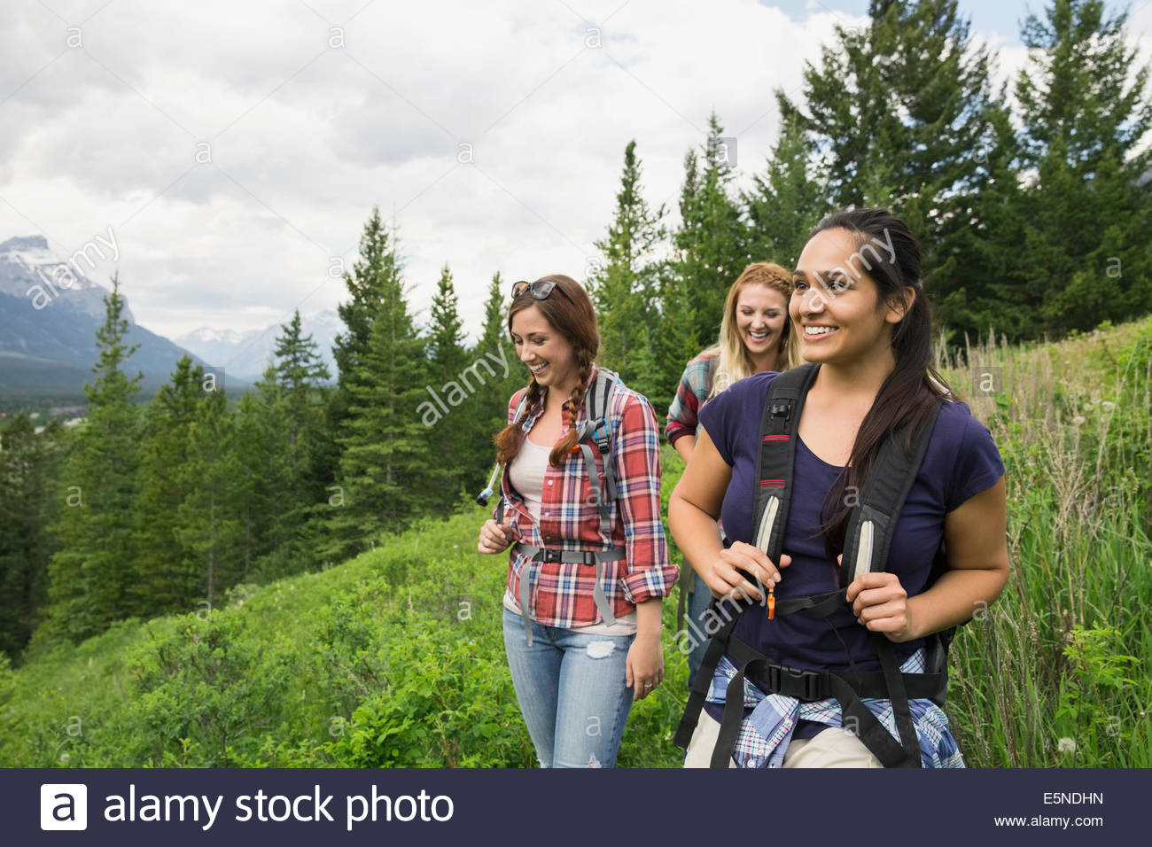 Friends hiking on trail near mountains - Stock Image