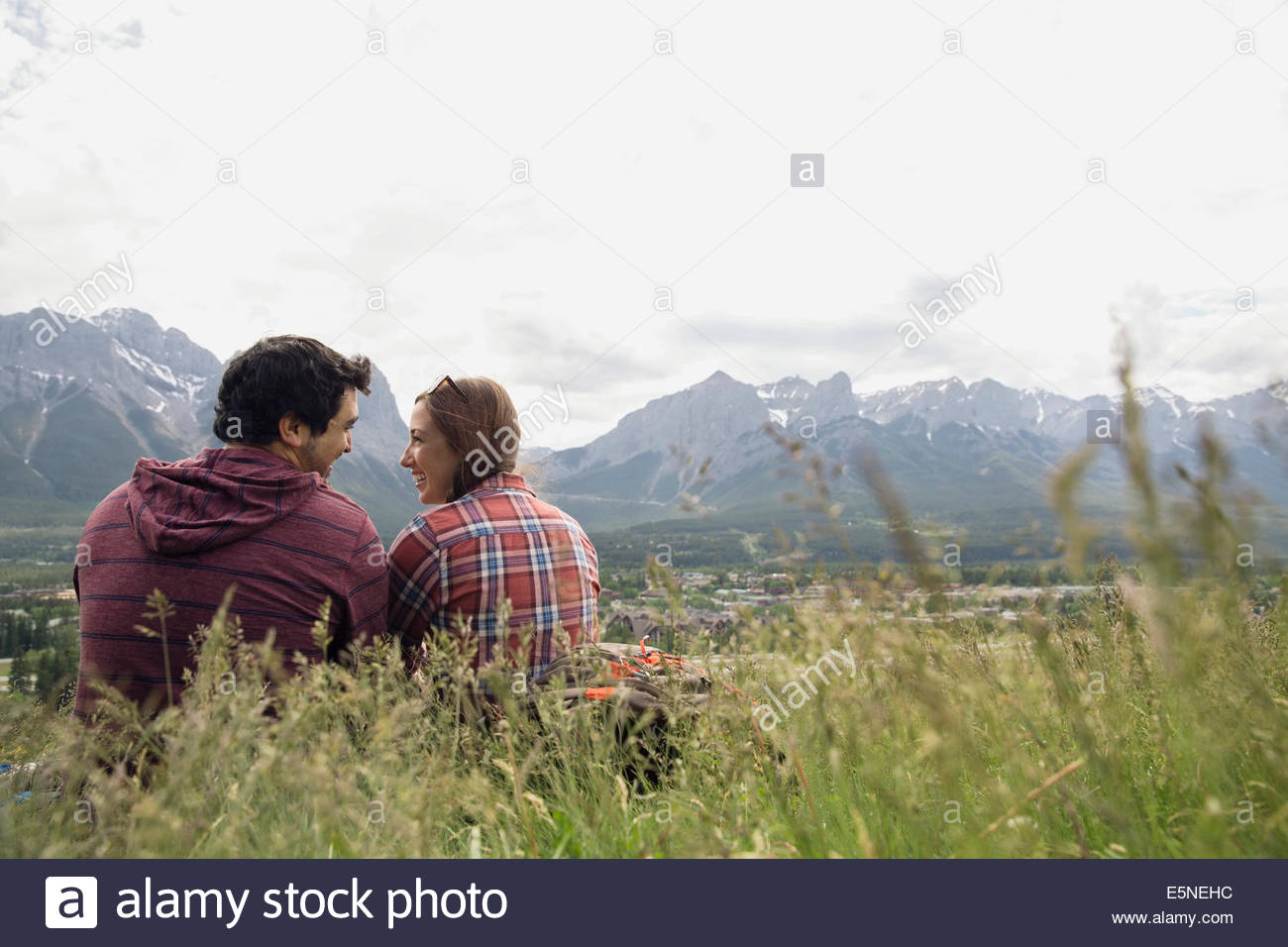 Couple sitting in grass with mountain view Stock Photo