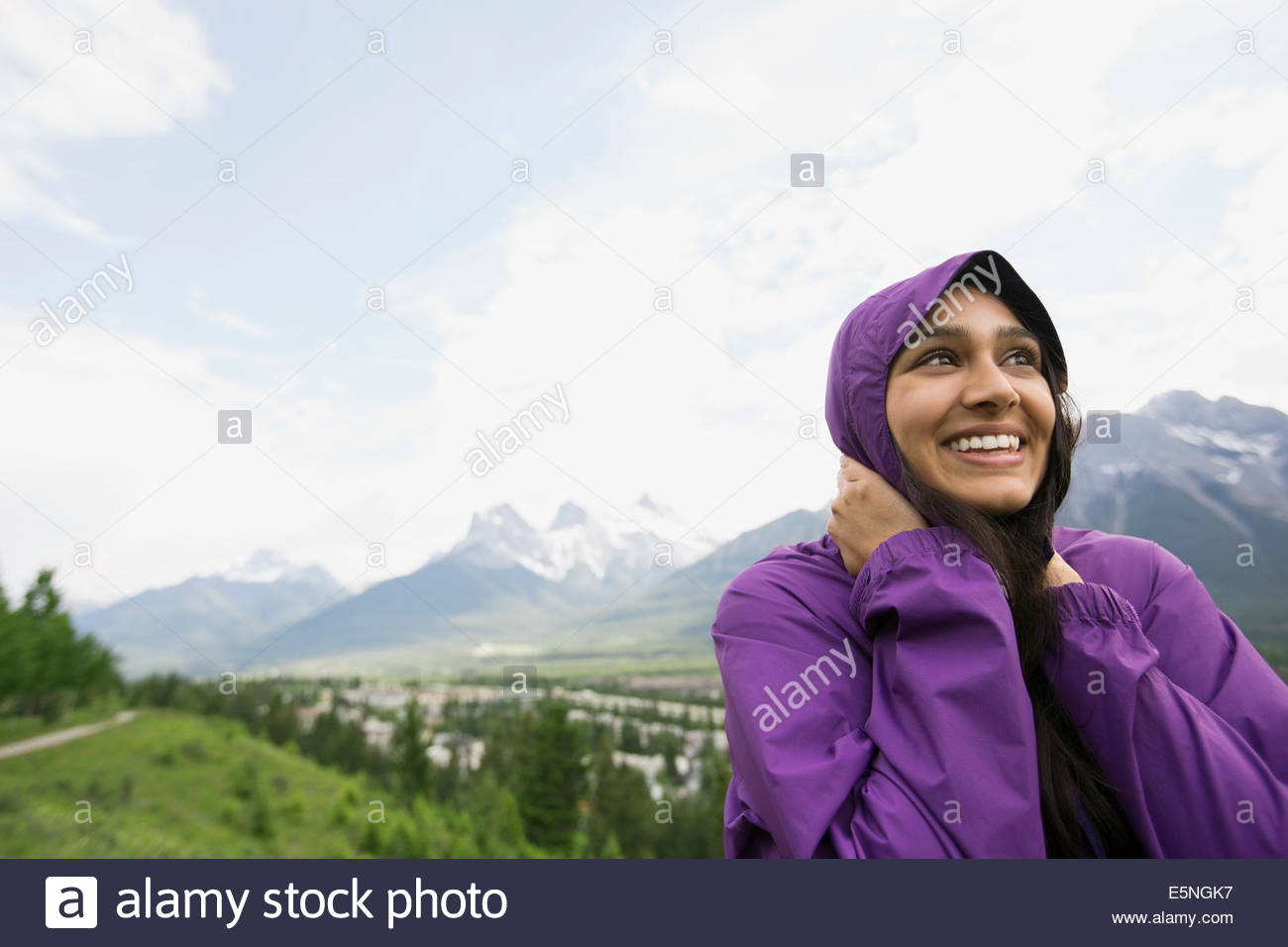 Smiling woman in hooded jacket near mountains - Stock Image