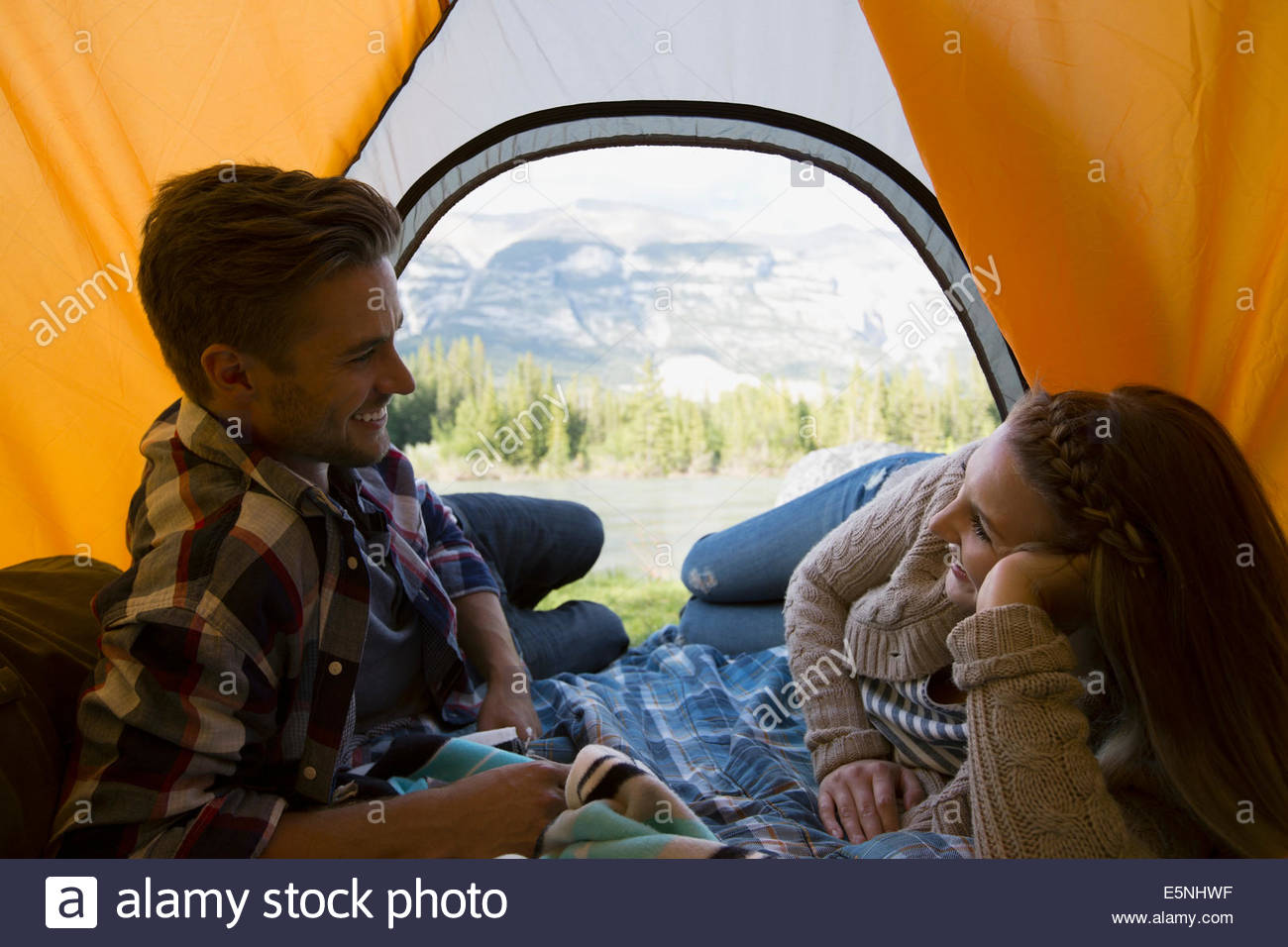 Couple laying in tent with mountain view - Stock Image