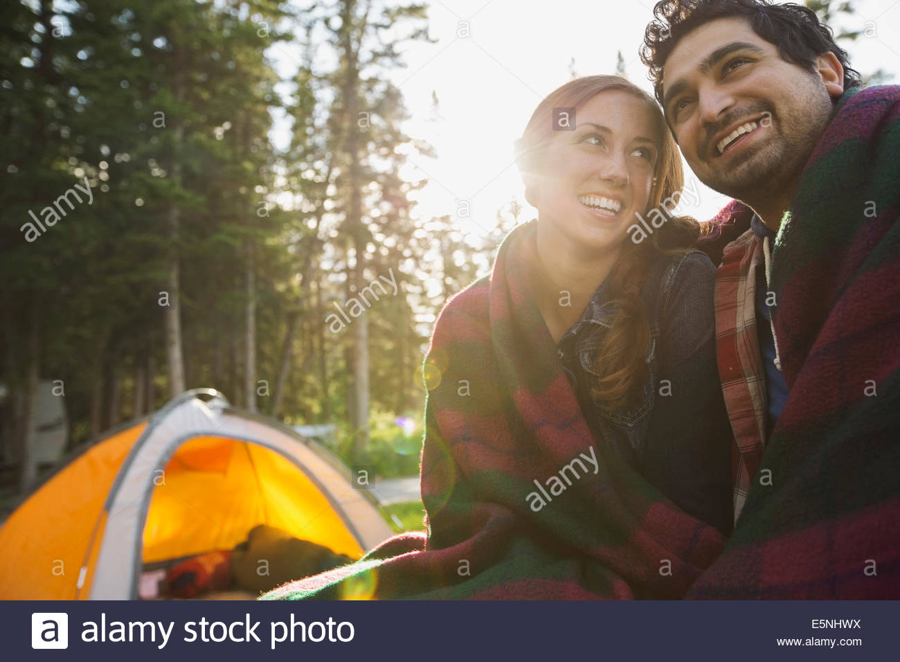 Couple wrapped in a blanket at campsite - Stock Image