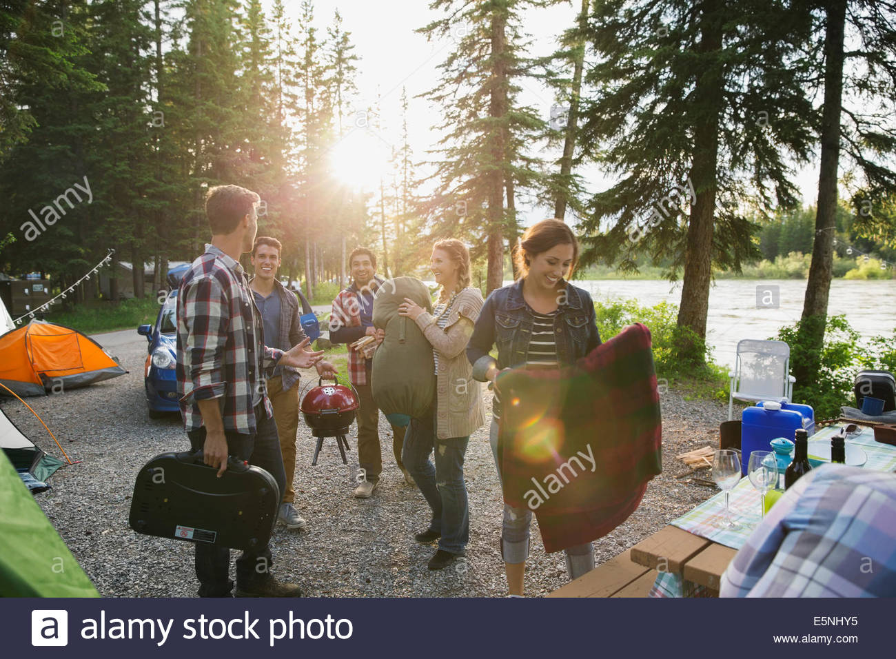 Friends with gear at campsite - Stock Image