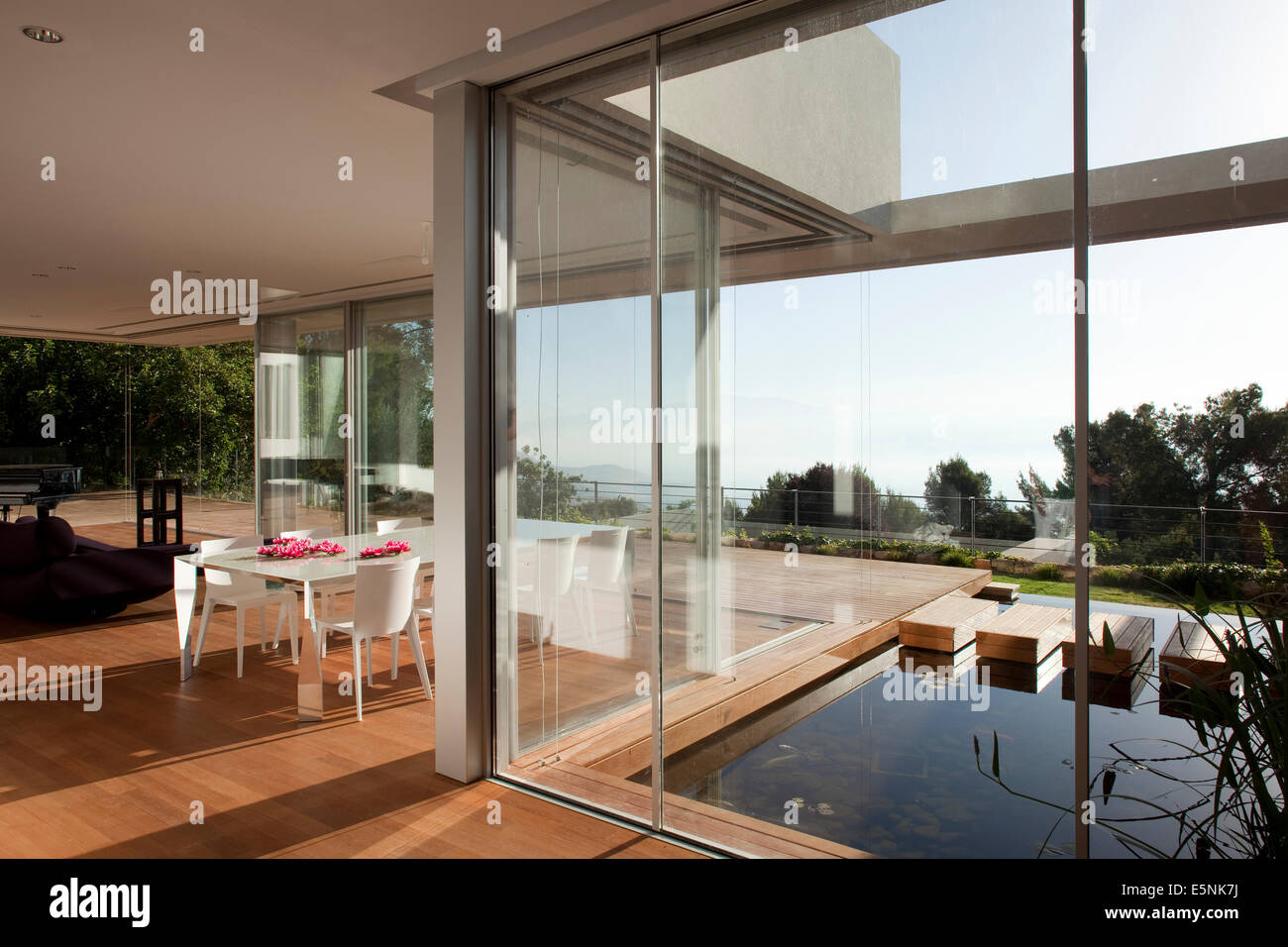full length windows small open plan dining room with view through full length windows to courtyard pool of house israel middle east stock