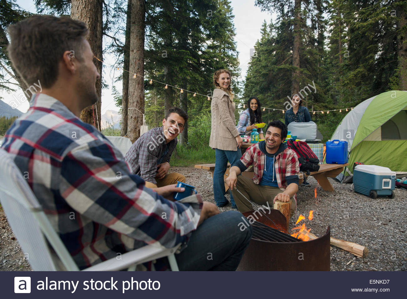Friends hanging out around campfire at campsite Stock Photo