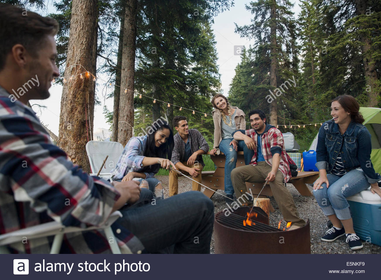 Friends hanging out around campfire at campsite - Stock Image