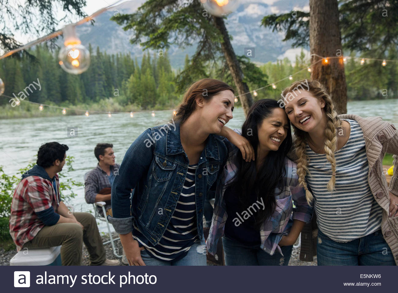 Girls laughing at lakeside campsite - Stock Image