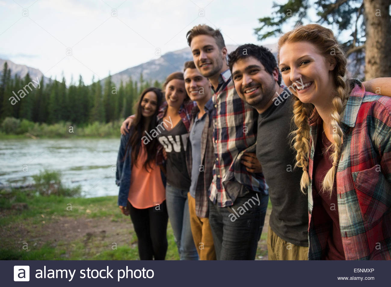 Portrait of friends in a row at lakeside - Stock Image