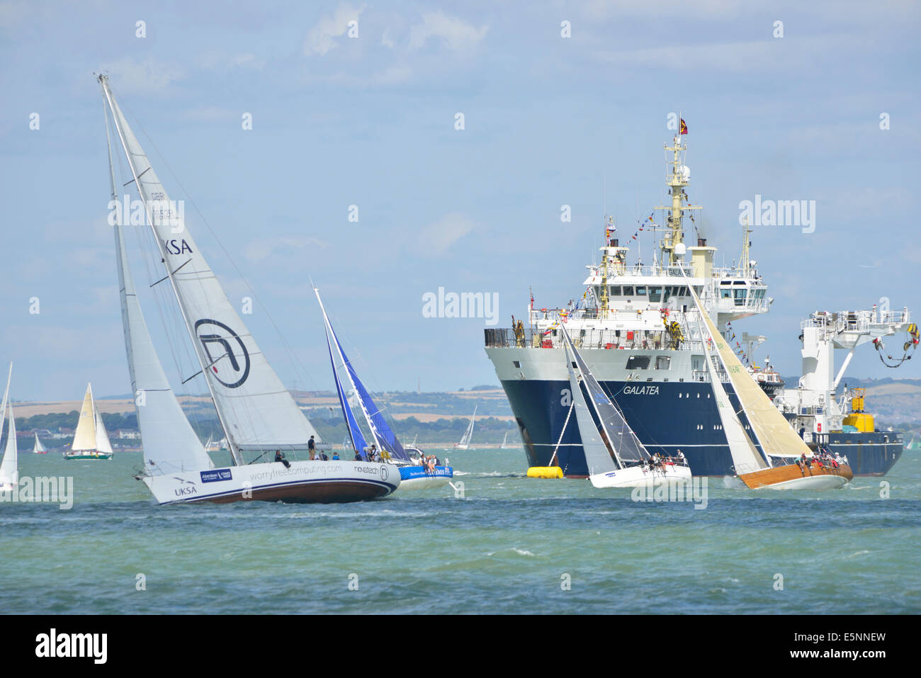 Yachts race in front of THV Galatea  moored of Cowes .Trinity House's Multi Functional Tender (MFT), GALATEA,is - Stock Image