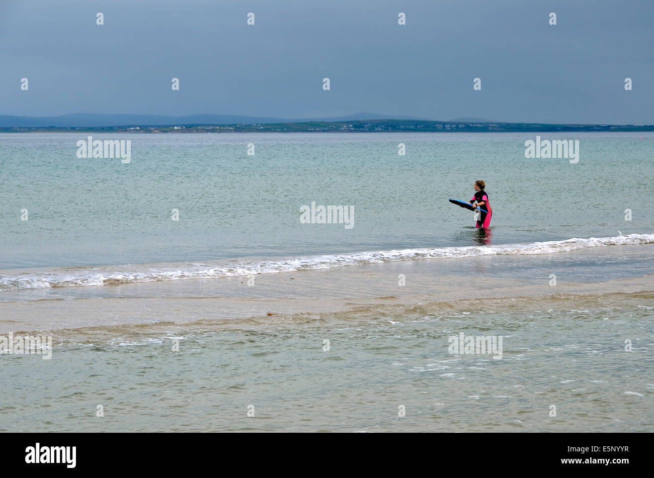 A surfer waits in vain for a wave on a flat calm sea, Silver Strand, Achill Island, County May, Ireland. - Stock Image