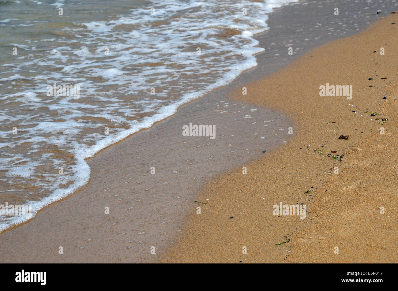Sea and sand - water lapping onto a sandy beach. - Stock Image