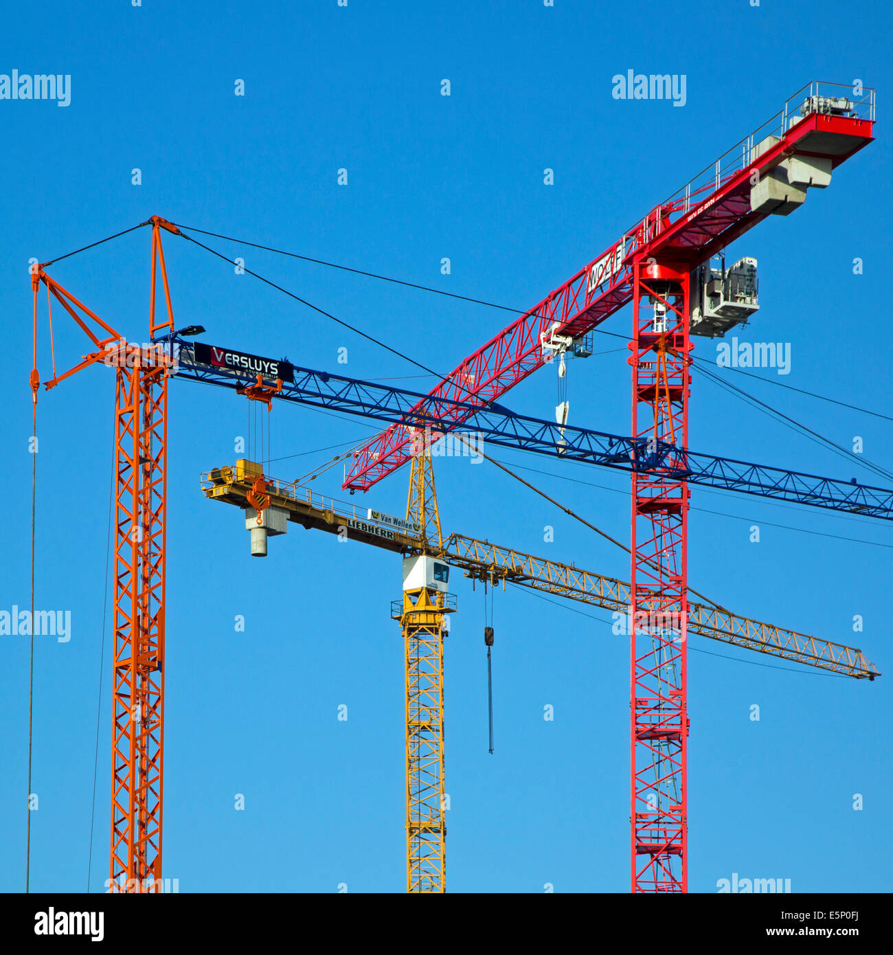 Three construction cranes / tower crane against blue sky - Stock Image