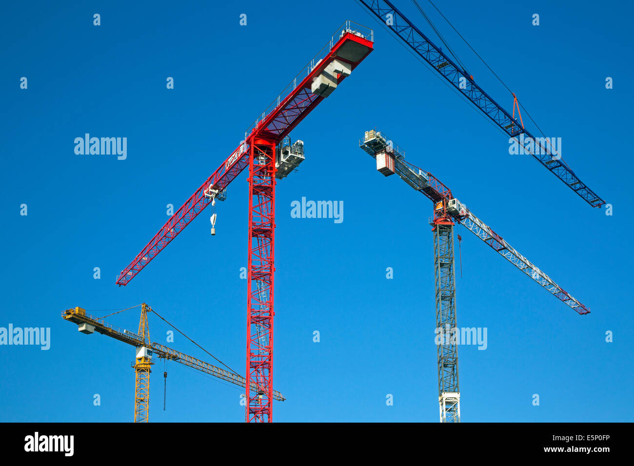 Construction cranes / tower crane against blue sky - Stock Image