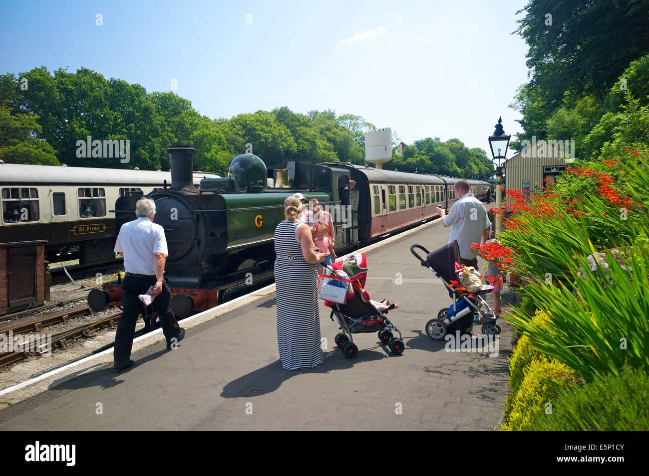 Passengers watch a steam train arrive at Bodmin General station on the Bodmin and Wenford Railway, Cornwall, UK - Stock Image