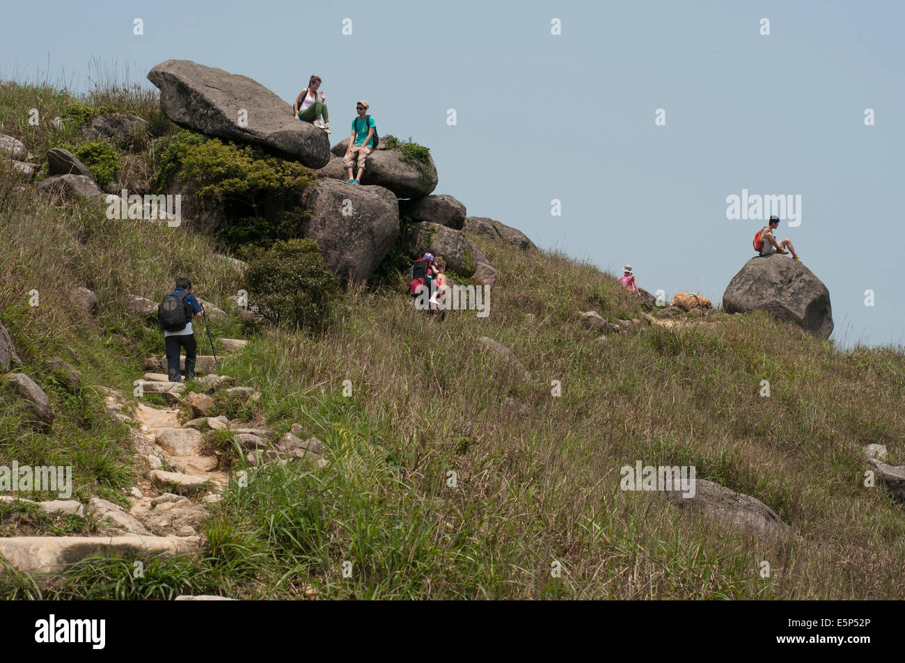 Hikers rest on the trail accessing the top of Sunset Peak Tai Tung Shan on Lantau Island Hong Kong, China. - Stock Image
