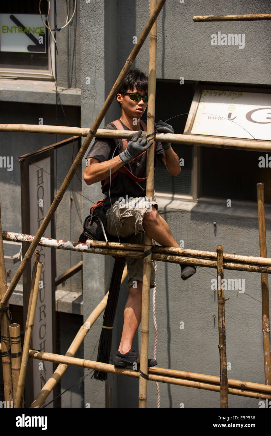 Hong Kong worker tying bamboo together to create a scaffold. Stock Photo