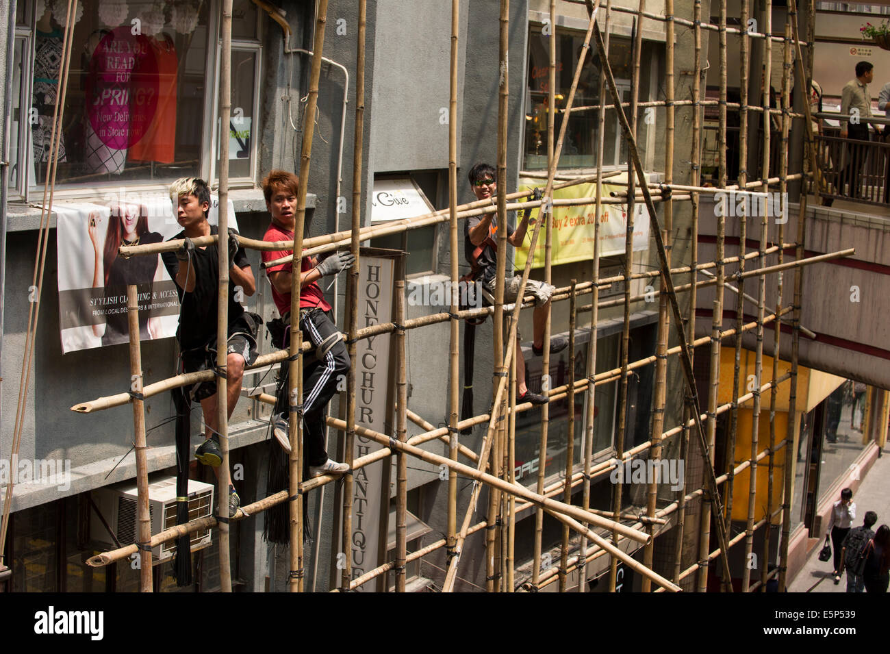 Hong Kong workers tying bamboo together to create a scaffold. - Stock Image