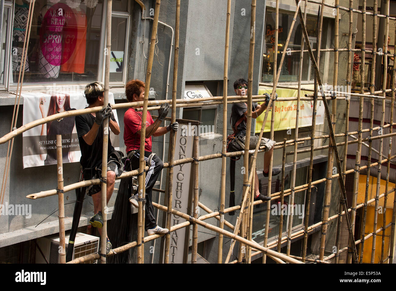 Hong Kong workers tying bamboo together to create a scaffold. Stock Photo
