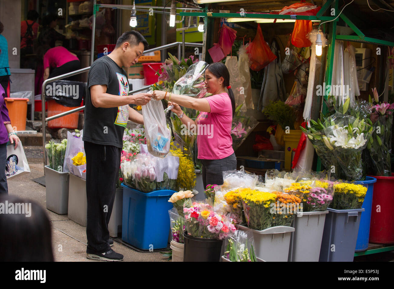 Man buying flowers from a Hong Kong street flower stand. - Stock Image