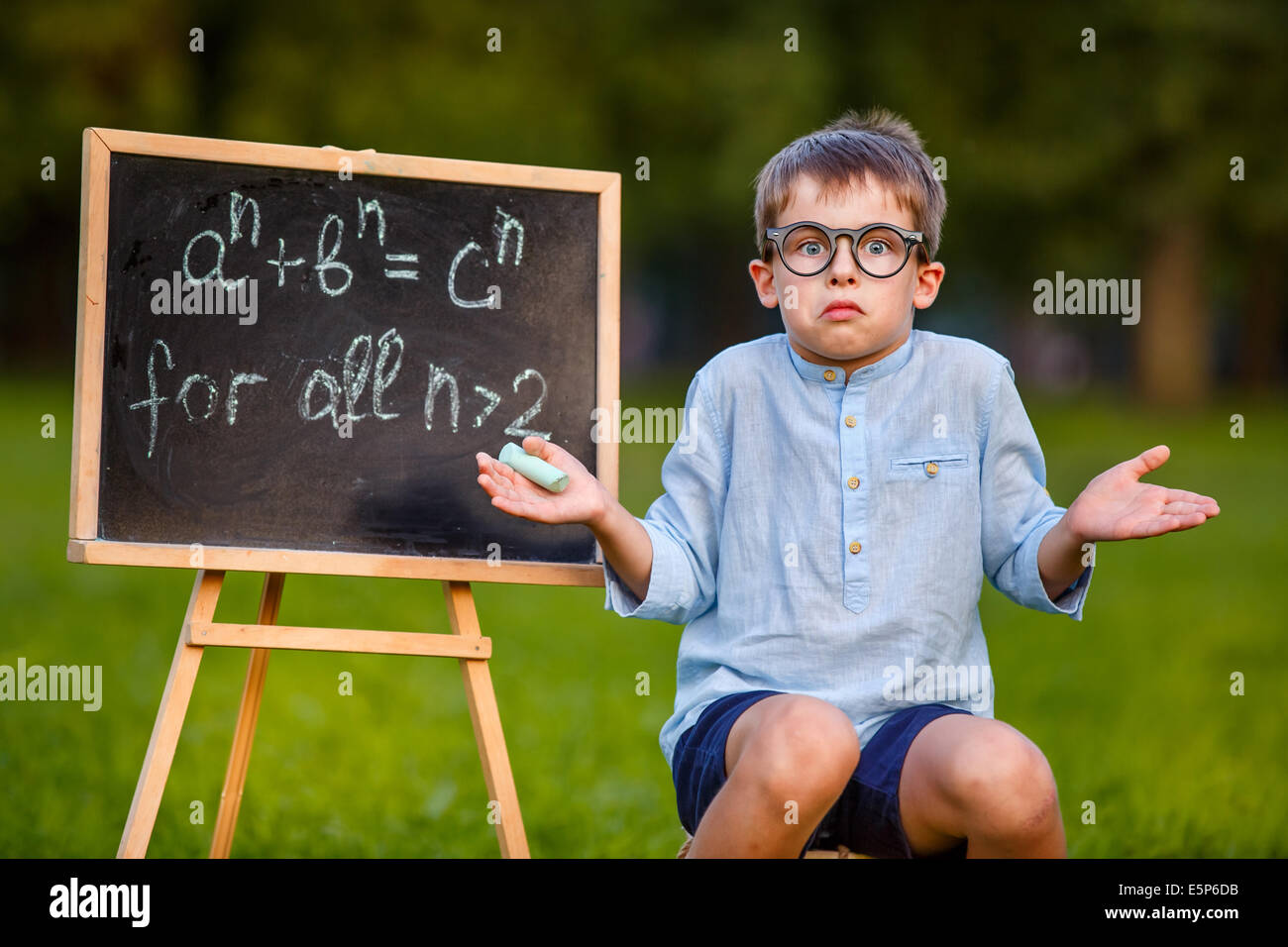 Cute little confused student shrugging his shoulders has no answer, thinking, puzzled - Stock Image